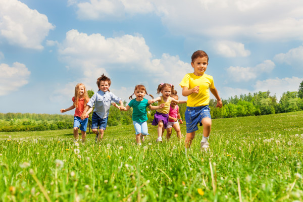 Running happy kids in green field during summer time