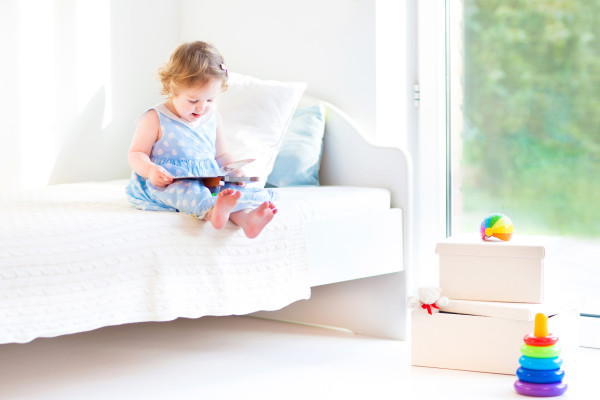 Adorable toddler girl reading a book sitting on a white bed at a