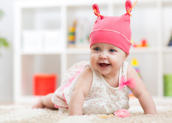 Smiling baby child crawling on nursery room floor