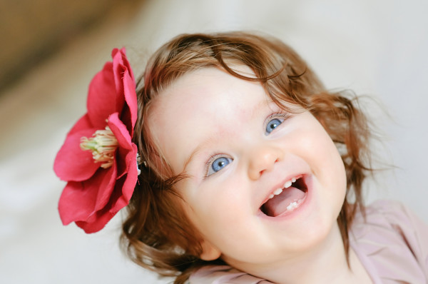 happy baby girl with flower on her hair smiling close-up