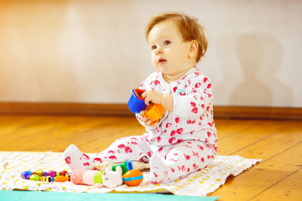 Portrait of cute infant girl playing with toy blocks at floor background.